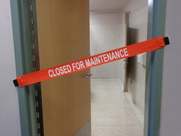 """Closed for Maintenance"""" Banner on a Bathroom"""