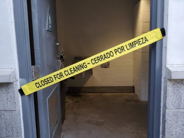 """Small Image of a """"Closed for Cleaning Banner Placed on a Bathroom Door"""