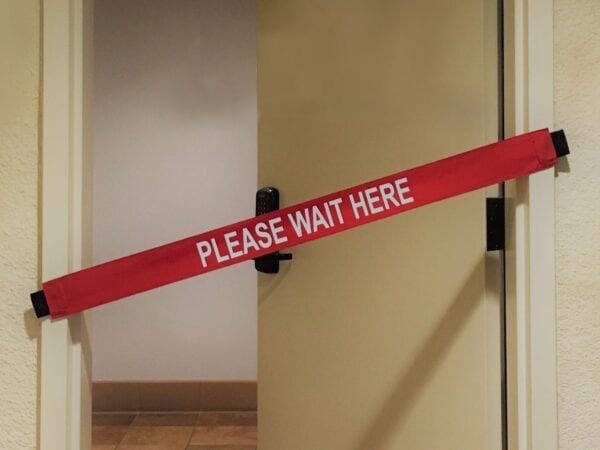 """A """"Please Wait Here"""" Banner On a Door"""